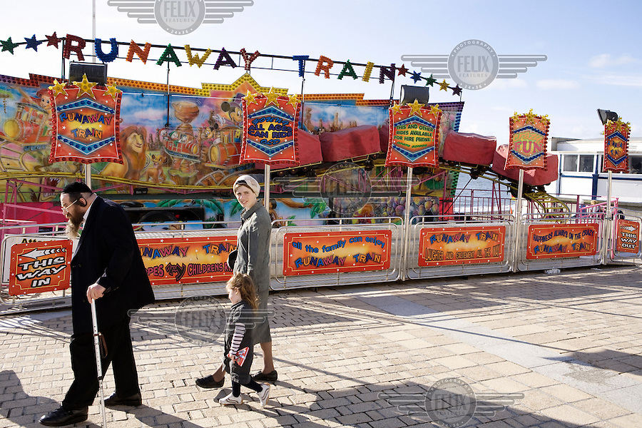 An Hasidic family walk past a fairground ride along the beach in Aberystwyth.