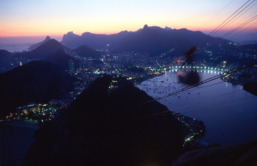 The cable car to the top of Rio de Janeiro's promontory Sugarloaf rock passes through the sunset over Brazil's second-largest city.