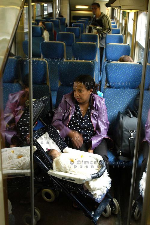 Roma,Ottobre 2005.Linea ferroviaria Roma-Nettuno.donna immigrata con figlio.Rome, October 2005.Railway line Roma-Nettuno.immigrant woman with son