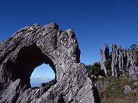 August 8th, 2004_ Mount Matebian, Timor-Leste_ The tops of clouds can be seen through a hole carved over the centuries in a rock outcrop on the slopes of Mt. Matebian.  Photograph by Daniel J. Groshong/Tayo Photo Group