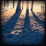 Shadows project on the sand under the Venice Beach pier.