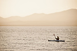 Woman kayaking at sunset on Lake Almanor, California.