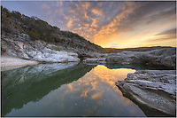 Sunrise comes to Pedernales Falls State Park. The colors of the sky light up the waters and rocks of the Texas Hill Country on a February morning.