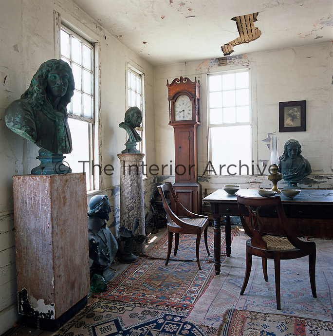 Busts of Moliere, Richelieu and Voltaire loom over the crumbling drawing room