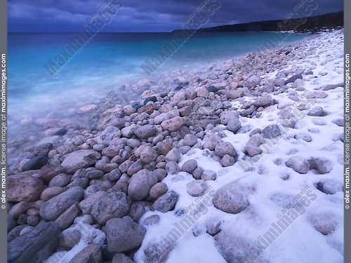 Pebbles on a shore of Georgian Bay covered with light snow. Wintertime scenic landscape. Bruce Peninsula National Park, Ontario, Canada.