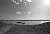 An earthwork by the artist Robert Smithson, consisting of a 140 foot diameter partial circle of rock, which rises out of the level ground to a height of around 15 feet. An artificial lake was created to surround it. The lake has long since been dry and the sculpture is now eroding. Smithson was killed in a plane crash while surveying the site for this work, along with a photographer and the pilot. The crash site is a few hundred yards from the Ramp. The completion of the piece was performed by his widow, Nancy Holt, Richard Serra, and others, shortly after his death in 1973. It was commissioned by Stanley Marsh, a local ranch owner and bon-vivant who also commissioned the famous Cadillac Ranch and several other sculptures on the over 200 square miles of land he owns with his wife around Amarillo.
