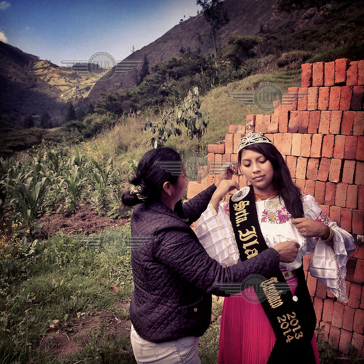 Maria Lara prepares her daughter Maria Alejandra Lara,16, for a photograph after Alejandra was named 'Senorita Ilalo' in the election of the Queen of Tumbaco. She is wearing traditional indigenous clothing from Cayambe and is standing on her grandfather's land on Ilalo, an extinct volcano.