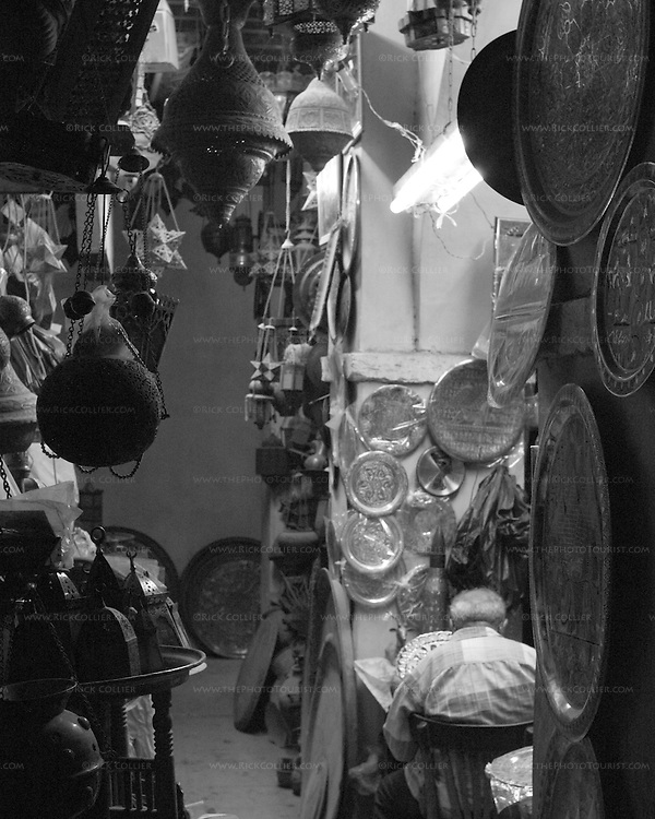 Workers in a brass Shop after dark, near closing time.   The Khan el-Khalili in central Cairo was once the market terminus for caravans crossing the Sahara.  Today, it is a warren of narrow streets and alleys, crowded with restaurants, tea rooms, stalls, and shops selling everything from jewelry to clothing to souvenirs and home decorations.  © Rick Collier.......Egypt Cairo Khan 'Khan el-Khalili' 'Khan al-Khalili' shop store Islamic Cairo stalls stands shopping tourism tourist historic history streets 'street scene' brass store bazaar engraving workman working tired fatigue evening dark night