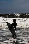 Man holding surfboard stands in knee deep water and waits to catch a wave.