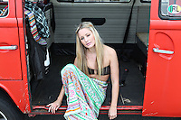A young woman sits in the doorway of a van at the beach.