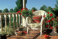 Front porch in the sun: White wicker chair set up with books, food, and a perfect blue sky day, Missouri USA