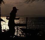 Silhouette of Asian worker pushing wheelbarrow,Pattaya, Thailand.