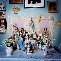A Candomble altar in the house of Mai Filinha, the Perpetual Judge (eldest member) of the Irmandade da Boa Morte (Sisterhood of the Good Death). The Sisterhood began as a bank in 1823, founded by freed slaves, to finance the freedom of men, women and children still bonded by slavery. The community, which is still made up of the descendents of slaves, is one of the oldest and most respected worship groups for Candomble, the major African-based religion in Brazil. The sisterhood practices a syncretised worship that combines Candomble, Catholicism and Islamic elements. Thanks to their microcredit scheme, and the two hundred religious events they organise throughout the year, the Sisterhood have achieved a central role in regional society, preserving some of the traditional African values that slavery brought to Brazil.