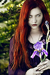 A girl with red hair holding a purple flower