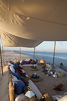 Preparations for an evening on the beach with impromptu sofas supported by banks of sand beneath a cotton awning