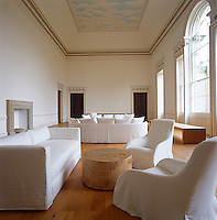 Minimal seating in white loose covers in a living room of classical Georgian proportions and with floor to ceiling windows