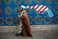 A cleric walks past a mural of a pistol in the colours of the US flag painted on the wall of the former US embassy in Tehran.