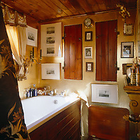 The walls of this tiny bathroom are covered in gold wrapping paper and hung with framed prints