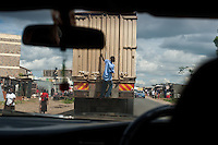 Nairobi, June 2010 -   Young male grabs a ride out of a Nairobi slum on the back of a container truck somewhere in Mathare district.
