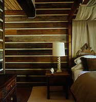A wooden four-poster bed with a carved headboard is framed by a natural linen canopy in this rustic bedroom