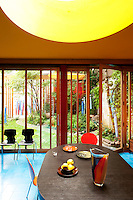 The dining table is positioned below a large round skylight cut into the yellow ceiling