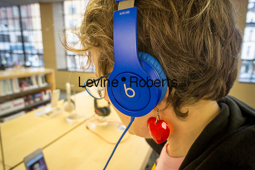 A customer tries on headphones by Beats Electronics in an Apple store in New York on Saturday, May 10, 2014. Apple announced that it will be buying Beats Electronics, the maker of the popular hip Beats by Dr. Dre audio equipment, for $3.2 billion. .  (© Richard B. Levine)