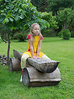Green, grass, lawn and seating. Caucasian girl sitting on old wooden bench in backyard. Serious mood.