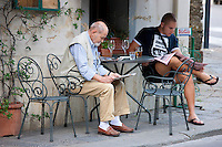 Locals reading at cafe in Montalcino, Val D'Orcia,Tuscany, Italy