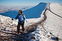 Female hiker hiking path towards Corn Du from Pen Y Fan in winter, Brecon Beacons national park, Wales