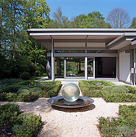 A water feature with a glass globe stands in the centre of a small garden laid with gravel and box hedge