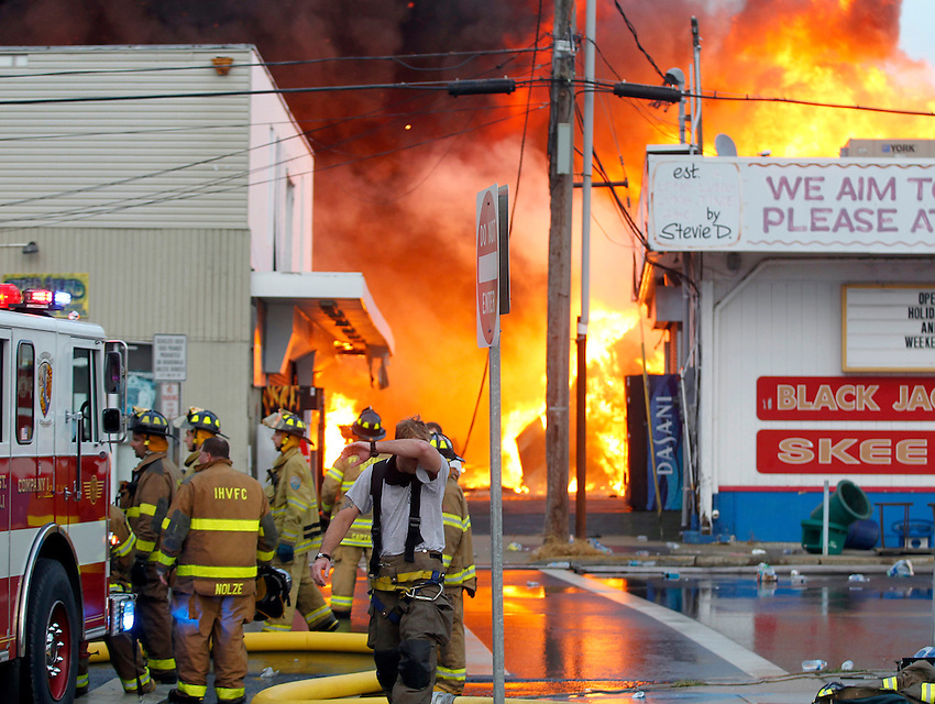 Firefighters pull back as a fast moving fire consumes the entire south end of the Seaside Boardwalk.  9/12/2013
