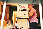 Jonah Corbett sits in a theater chair as his mom votes at Masonic Temple in Los Altos, CA.