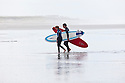 WA09812-00...WASHINGTON - Surfers at Westhaven State Park near Westport.