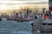 Gillnet fishing boats jockey for positions to make a set  for sockeye salmon during ebb tide on the North Line fishing boundary of Egegik River in Bristol Bay, Alaska in July 1996.  Bristol Bay is home to the world?s largest sockeye salmon fishery.  The commercial salmon drift gillnet fishing fleet is limited to boats no longer than 32 feet in length.  There were over 1,800 permanent entry permits listed in 2002 which each vessel is required to have.  Typically boats fish with two or three deckhands.  Peak of the season is around July 4th in this fishery which lasts about a month. The rivers also get a fair amount of chum, king, and chinook salmon. Bristol Bay is located in the southwest part of Alaska. This fishery is managed by ?the Alaska Department of Fish and Game? and is a sustainable fishery.  Until around the year 2000, fishing on the Egegik North Line was lively and lucrative..