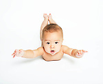 Human baby, 6-9months, on stomach with head, arms and legs up, looking at camera.
