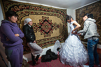 Dinara is helped into her wedding dress by relatives and friends on the day of her wedding. Dinara was kidnapped by Ahmat who wanted to marry her. After resisting for 5 hours, she finally accepted. 'I didn't know Ahmad well and didn't want to stay there. But I accepted because this is our tradition' Dinara says. Although illegal, bride kidnapping is common in rural parts of Kyrgyzstan. Each year around 16, 000 women become married after being kidnapped. They are known as 'Ala Kachuu' that translates as 'to grab and run away'. Defenders of the continuation of the practice sight tradition. However, during Soviet Times it was rare, and parents generally arranged marriages..