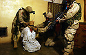 U.S. Army soldiers from the 82nd Airborne 1st Battalion 505th Regiment secure a an Iraqi detainee during an October 31, 2003 cordon and search operation through three houses in the town of Fallujah, Iraq.