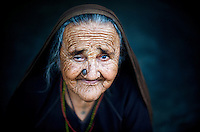 An extremely old Rabari woman sitting in her courtyard. She is extremely old as the wrinkles of her face suggest.
