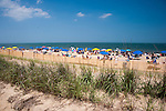 Sunbathers and vacationers enjoy the beach beyond the sand dunes and fences on the first day of summer at Rehoboth Beach, Delaware, USA.