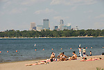 Minnesota, Twin Cities, Minneapolis-Saint Paul: Recreation at the south end of Lake Calhoun, with the Minneapolis skyline in the background.  Women beach bathers..Photo mnqual275-75198..Photo copyright Lee Foster, www.fostertravel.com, 510-549-2202, lee@fostertravel.com.
