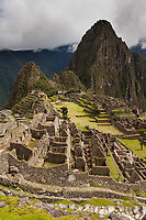 """Huayanapichu (young mountain) in the distance at Machu Picchu, the ancient """"lost city of the Incas"""", 1400 CA, 2400 meters. Discovered by Hiram Bingham in 1911. One of Peru's top tourist destinations."""