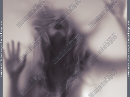Dramatic photo of a young woman blurred silhouette trying to break through glass barrier