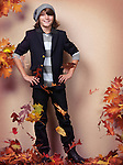 Smiling boy wearing fall clothes, standing on fallen red leaves, autumn children fashion photo