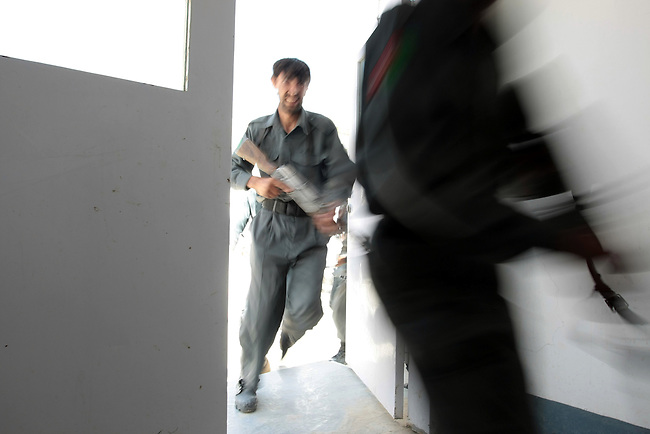 Afghan police rush through a door, as they practice clearing a building during a U.S.-led training session near the city of Qalat, in Zabul province, Afghanistan. Aug. 25, 2008. DREW BROWN/STARS AND STRIPES