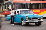 Havana, Cuba; a classic teal blue and white 1955 Plymouth serves as a taxi along the Paseo de Marti
