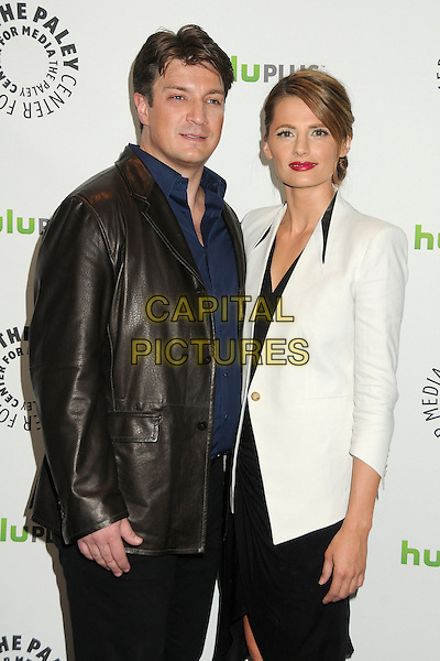 """Nathan Fillion, Stana Katic.PaleyFest 2012 Presents """"Castle"""" held at The Saban Theatre, Beverly Hills, California, USA, 9th March 2012..half length leather jacket white blue shirt dress black .CAP/ADM/BP.©Byron Purvis/AdMedia/Capital Pictures."""
