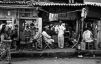 woman walks past barber shops on the streets on Mumbai, India.  January, 2000