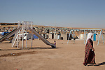 DOMIZ, IRAQ: A woman walks past a slide in the Domiz refugee camp...Over 7,000 Syrian Kurds have fled the violence in Syria and are living in the Domiz refugee camp in the semi-autonomous region of Iraqi Kurdistan...Photo by Ali Arkady/Metrography