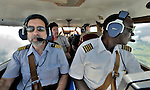 Stephen Quigg (left), a United Methodist missionary assigned to Mission Safety International, consults with pilot Jacques Umembudi Akasa, a United Methodist missionary assigned to Wings of Caring, in the cockpit of a flight from Kananga to Kamina, in the Democratic Republic of the Congo. Wings of Caring is a program of the United Methodist Church.