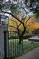 A gate and path lead to an office building's courtyard filled with autumn colors.